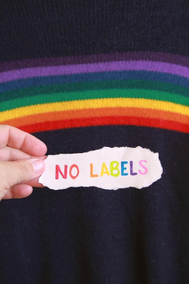 finger holding paper rainbow background